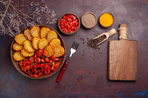 Vista dall'alto di patate al forno con verdure cotte e condimenti in uno spazio buio