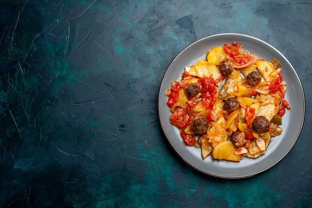 Вид сверху запеченный картофель с фрикадельками и овощами внутри тарелки на синем фоне.