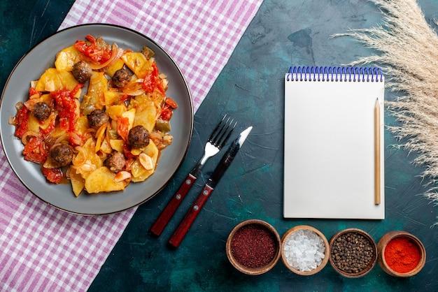 Vista dall'alto di patate al forno con polpette di carne e verdure insieme a condimenti su sfondo blu scuro.