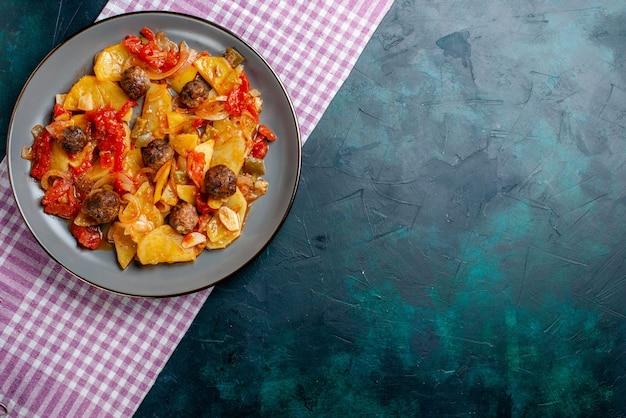Vista dall'alto di patate al forno con polpette di carne e verdure all'interno del piatto su sfondo blu scuro.