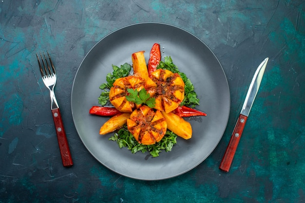 Вид сверху запеченный картофель с фаршем и зеленью внутри тарелки на темно-синем столе.