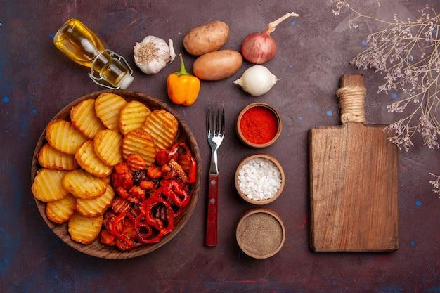 Vista dall'alto di patate al forno con condimenti su uno spazio buio
