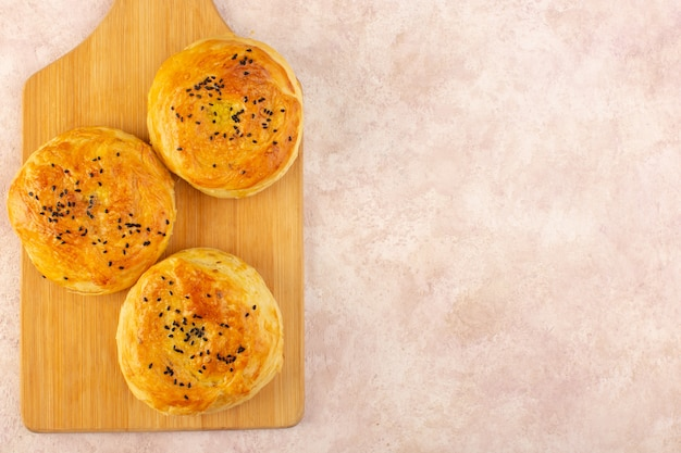 A top view baked qogals round shaped tasty hot fresh off the oven on the brown desk