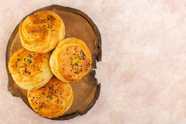 A top view baked qogals round shaped tasty hot fresh off the oven on the brown wooden desk