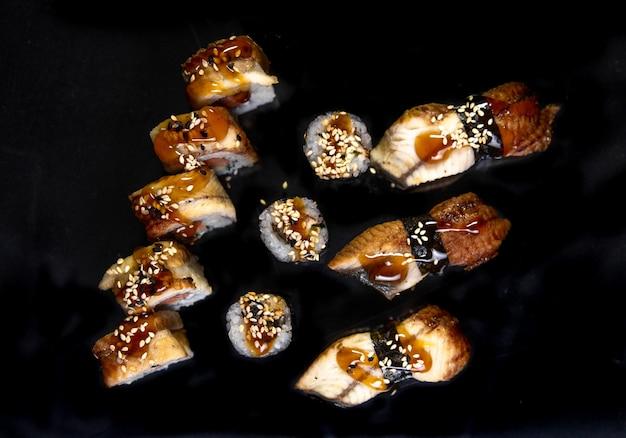 Вид сверху запеченные роллы и суши на черном