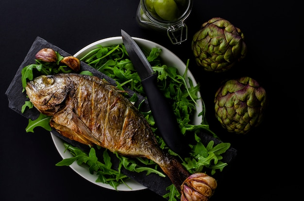 Top view of baked sea bream on a bowl with arugula, artichokes and knife on black background