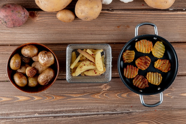 Top view of baked sliced potato with potato chips on wooden background with copy space