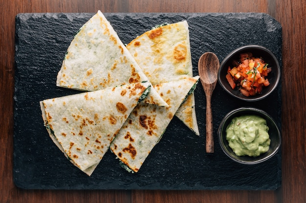 ฺtop view of baked spinach and cheese quesadillas served with salsa and guacamole.