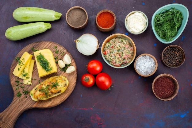 Zucche al forno vista dall'alto con carne macinata di verdure al formaggio e verdure fresche sulla scrivania viola scuro.