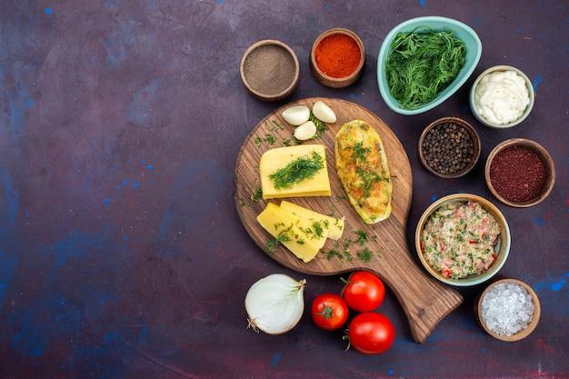 Vista dall'alto zucche al forno con verdure di formaggio condimenti carne macinata e verdure fresche sulla scrivania scura.