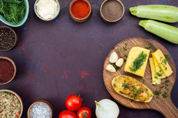 Vista dall'alto zucche al forno con verdure di formaggio condimenti carne macinata e verdure fresche sulla scrivania viola scuro.