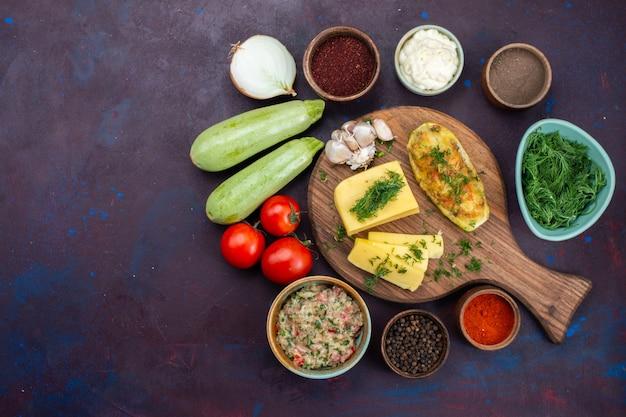 暗い机の上にグリーンチーズ調味料の肉と新鮮な野菜を添えた上面図焼きカボチャ。