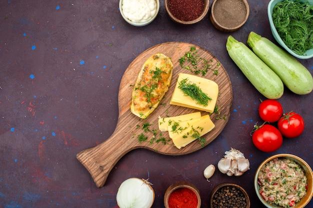 Zucche al forno vista dall'alto con verdure formaggio condimenti carne e verdure fresche sulla scrivania scura.