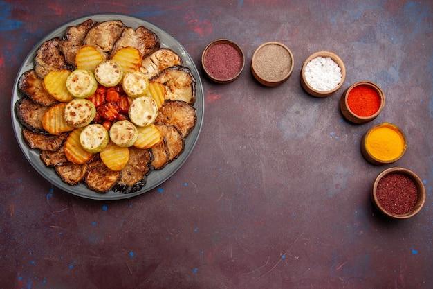 暗い空間でさまざまな調味料で焼き野菜ジャガイモとナスの上面図