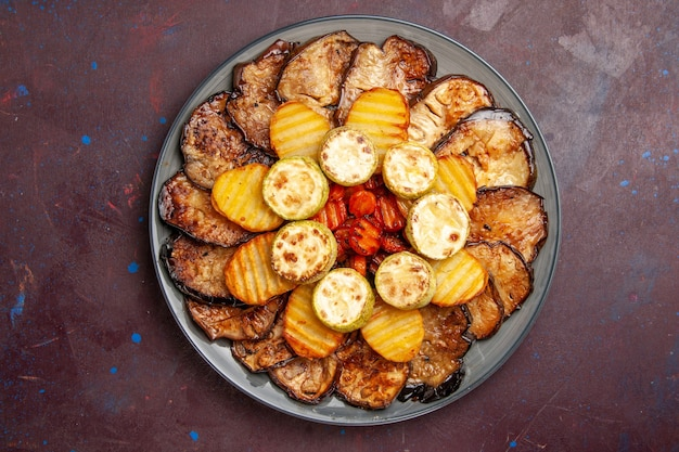 Top view baked vegetables potatoes and eggplants inside plate on dark space