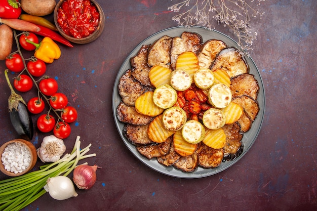 Top view baked vegetables potatoes and eggplants with different seasonings on a dark desk