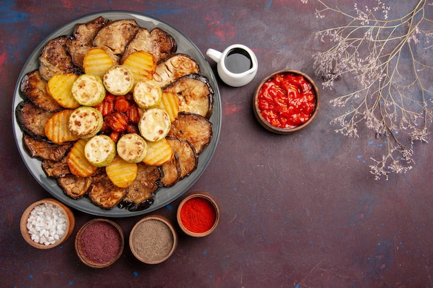 Top view baked vegetables potatoes and eggplants with different seasonings on a dark space
