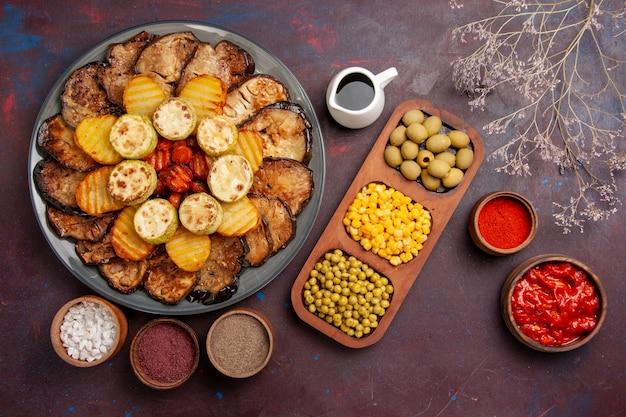 Vista dall'alto verdure al forno patate e melanzane con diversi condimenti su uno spazio buio