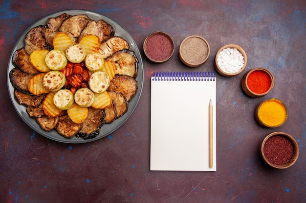 Top view baked vegetables potatoes and eggplants with different seasonings on dark space