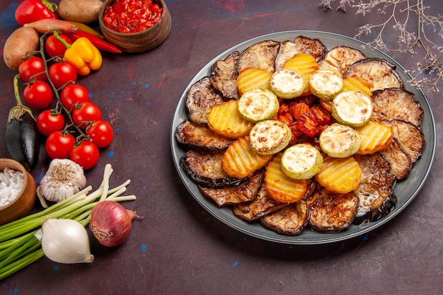 Top view baked vegetables potatoes and eggplants with fresh vegetables on dark space