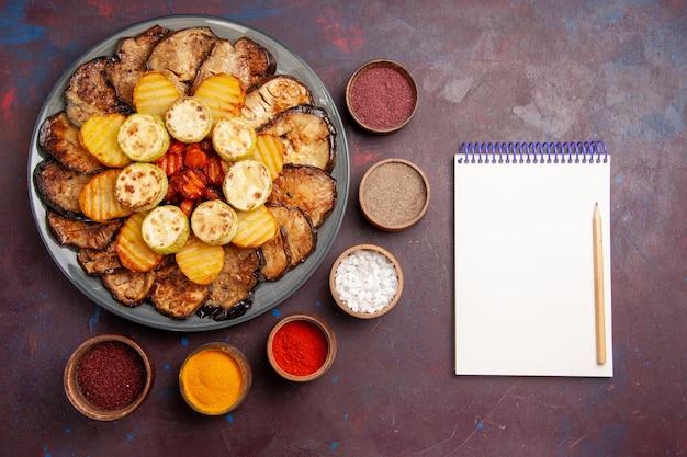Top view baked vegetables potatoes and eggplants with seasonings on dark space