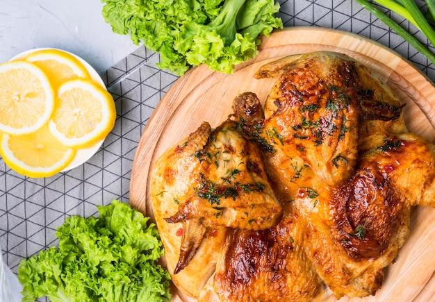 레몬 조각으로 커팅 보드에 구운 전체 치킨 상위 뷰