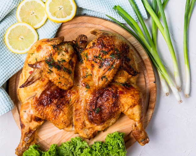 Top view baked whole chicken with lemon slices
