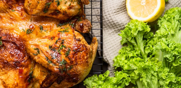 Top view baked whole chicken with salad and lemon