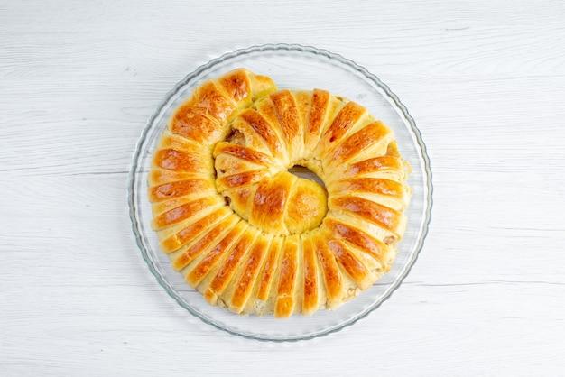 Vista dall'alto del braccialetto di pasta sfoglia al forno formata all'interno della piastra sulla luce, zucchero di pasticceria dolce da forno