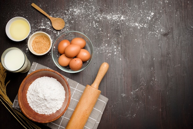 Top view of bakery ingredients on black wooden table