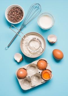 Вид сверху муки для выпечки с яйцами на столе