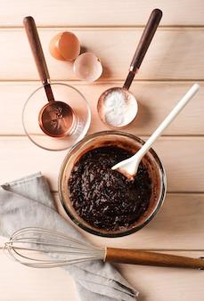 Приготовление для выпечки, вид сверху, смешанное шоколадное тесто на прозрачной миске с белым шпателем. приготовление пирожных или шоколадного кекса