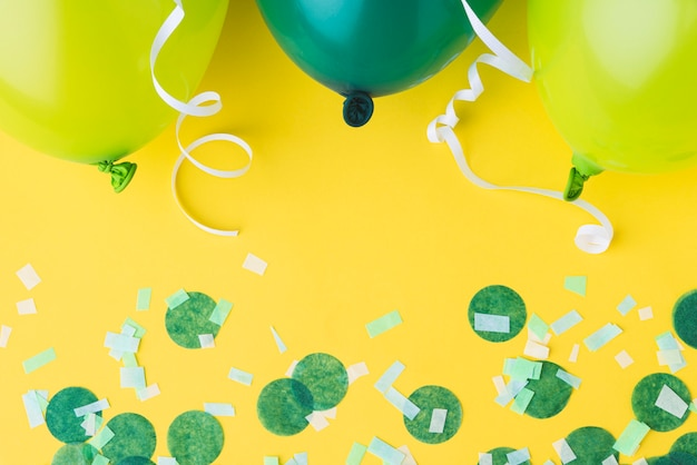 Top view of balloons and confetti frame on yellow background