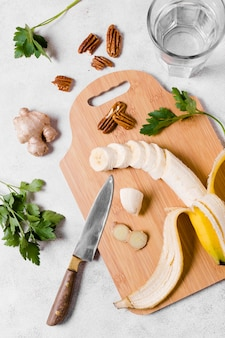 Top view of banana and ginger on chopping board