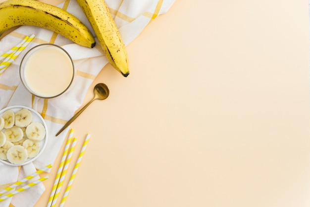 Top view of banana smoothie with straws and fruit
