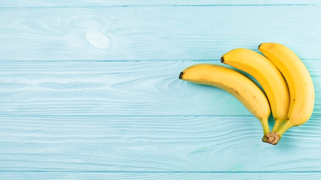 Top view of bananas on blue background with copy space