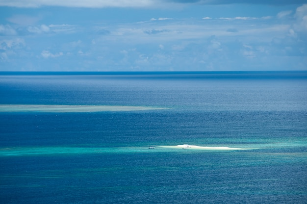 Top view of barasu coral island surrounded by a stunning deep blue sea