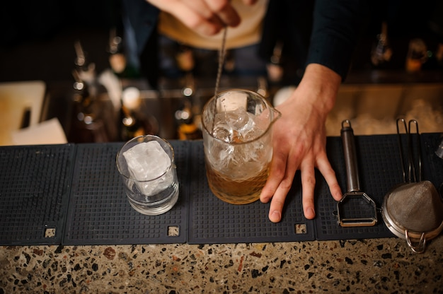 Top view of bartender hand stirring alcoholic cocktail with ice