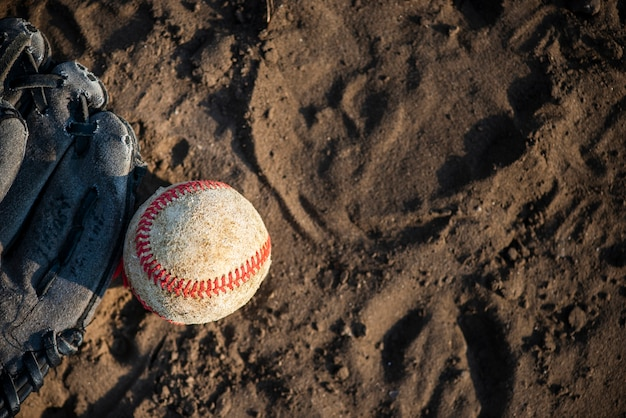 Top view of baseball and glove on dirt