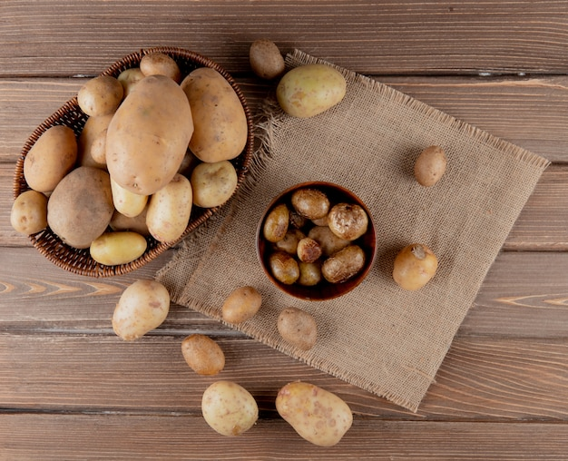 Top view of basket and bowl full of potato on sackcloth on wooden background with copy space