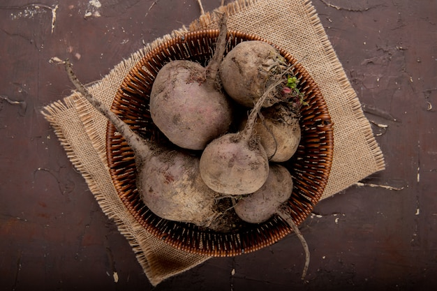 Top view of basket full of beetroots on sackcloth surface and maroon background with copy space