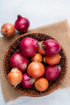 Top view of basket full of onions on sackcloth on white background