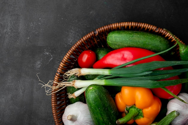 Top view of basket full of vegetables as scallion pepper cucumber and others on right side and black surface