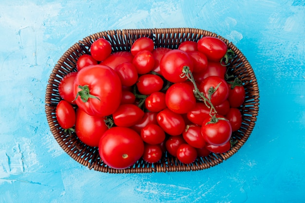 Top view of basket full of whole tomatoes on blue surface