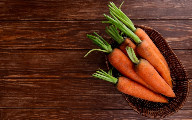 Top view of basket plate with carrots on wooden background with copy space
