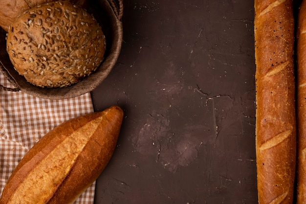 Top view of basket of seeded cob on cloth and baguettes on maroon background with copy space