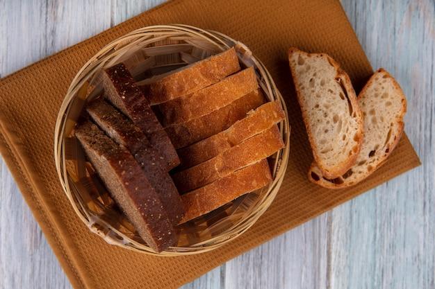Vista dall'alto del cesto di fette di pane come segale e quelli croccanti sul panno su sfondo di legno