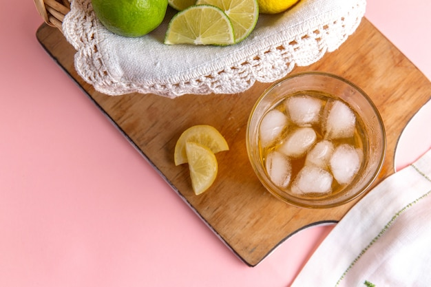 Top view of basket with citruses lemons and limes inside with iced drink on pink surface