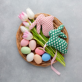 Top view of basket with easter eggs and tulips