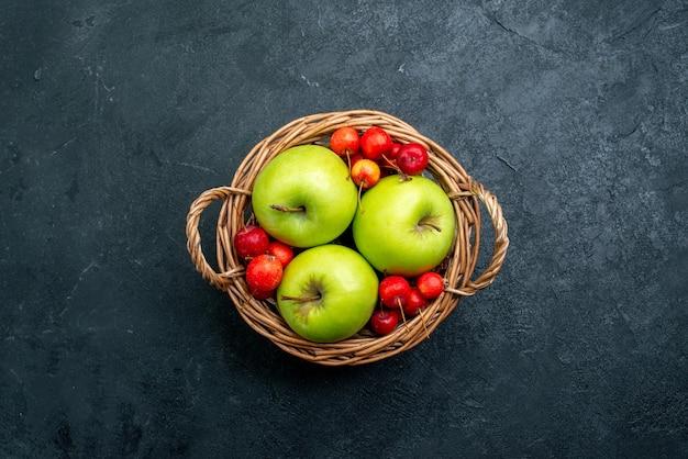 暗い表面のフルーツベリー組成フレッシュツリーにフルーツアップルとスイートチェリーのトップビューバスケット